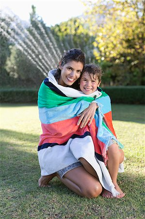 Mother and son wrapped in towel in backyard Stock Photo - Premium Royalty-Free, Code: 6113-06909394