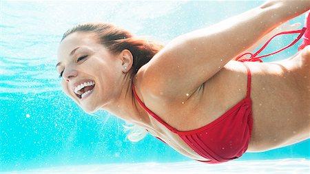 Woman swimming in pool Stock Photo - Premium Royalty-Free, Code: 6113-06909300