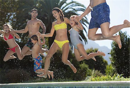 Family jumping into swimming pool Stock Photo - Premium Royalty-Free, Code: 6113-06909304