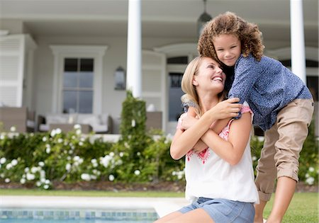 Mother and daughter hugging by swimming pool Stock Photo - Premium Royalty-Free, Code: 6113-06909308
