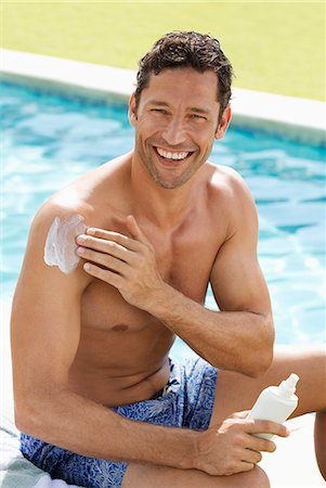 Man applying sunscreen by swimming pool Stock Photo - Premium Royalty-Free, Code: 6113-06909317