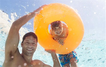 Father and son playing in swimming pool Stock Photo - Premium Royalty-Free, Code: 6113-06909318