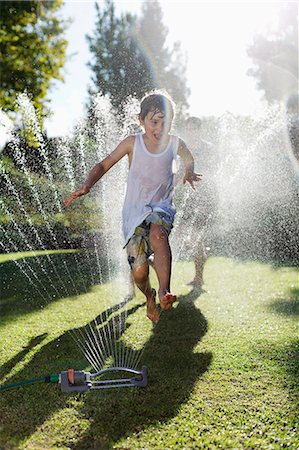 Boy playing in sprinkler in backyard Stock Photo - Premium Royalty-Free, Code: 6113-06909325