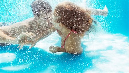 Couple kissing in swimming pool Stock Photo - Premium Royalty-Free, Code: 6113-06909329