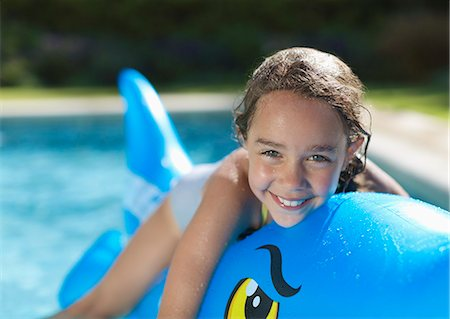 Girl riding inflatable toy in swimming pool Stock Photo - Premium Royalty-Free, Code: 6113-06909334