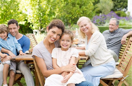 Family smiling at table outdoors Stock Photo - Premium Royalty-Free, Code: 6113-06909451