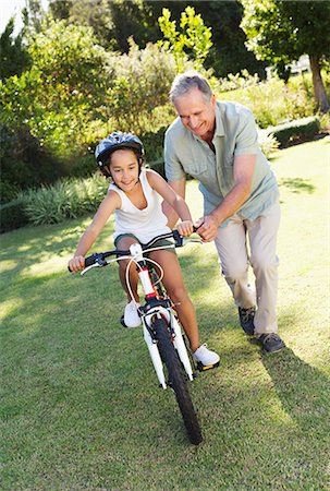 Older man teaching granddaughter to ride bicycle Stock Photo - Premium Royalty-Free, Code: 6113-06909467