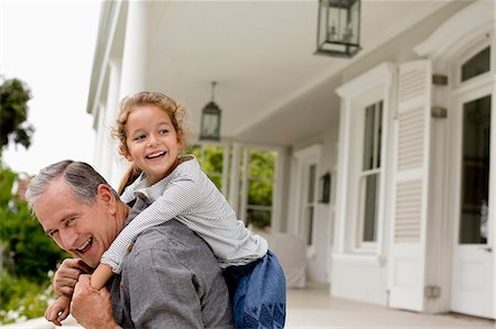 Older man carrying granddaughter piggy back on porch Stock Photo - Premium Royalty-Free, Code: 6113-06909423