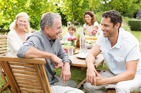 Family sitting at table outdoors Stock Photo - Premium Royalty-Free, Code: 6113-06909422