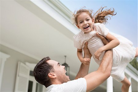Father and daughter playing outside house Stock Photo - Premium Royalty-Free, Code: 6113-06909427