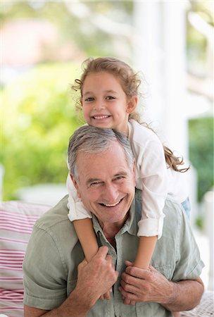 Older man carrying granddaughter piggyback Stock Photo - Premium Royalty-Free, Code: 6113-06909429