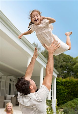 Father and daughter playing outside house Stock Photo - Premium Royalty-Free, Code: 6113-06909432