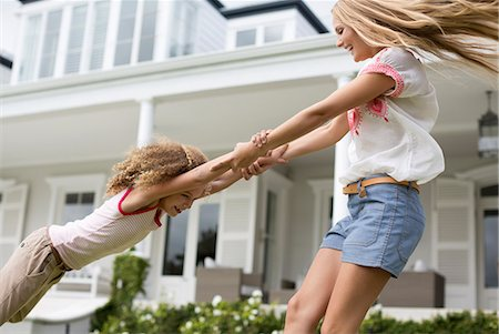 Mother and daughter playing outside house Stock Photo - Premium Royalty-Free, Code: 6113-06909439