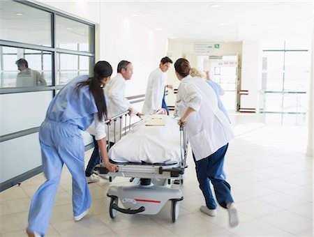 pushing - Doctors rushing patient on stretcher down hospital corridor Stock Photo - Premium Royalty-Free, Code: 6113-07146748
