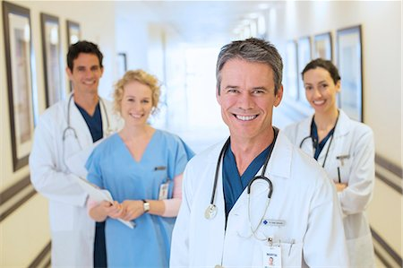 Portrait of smiling doctors and nurse in hospital corridor Stock Photo - Premium Royalty-Free, Code: 6113-07146757