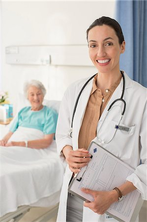 simsearch:6113-07146726,k - Portrait of smiling doctor with senior patient in background Stock Photo - Premium Royalty-Free, Code: 6113-07146760