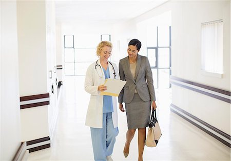simsearch:6113-07146726,k - Doctor and businesswoman talking in hospital corridor Stock Photo - Premium Royalty-Free, Code: 6113-07146780