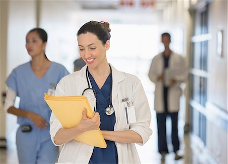 simsearch:6113-07146726,k - Doctor looking down at files in hospital corridor Stock Photo - Premium Royalty-Free, Code: 6113-07146787