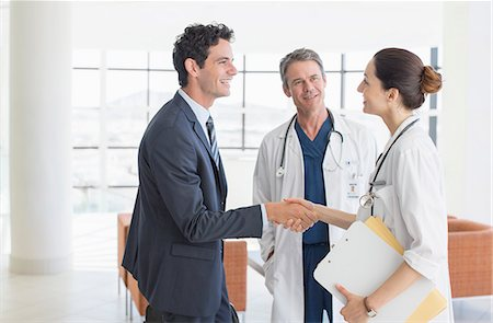 partnership - Doctor and businessman handshaking in hospital lobby Stock Photo - Premium Royalty-Free, Code: 6113-07146784