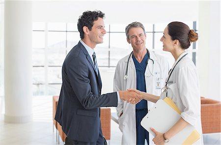 partnership - Doctor and businessman handshaking in hospital lobby Stock Photo - Premium Royalty-Free, Code: 6113-07146784