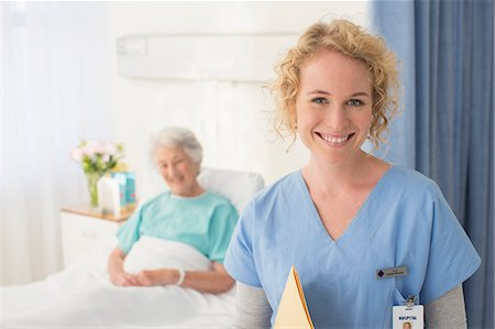 simsearch:6113-07146726,k - Portrait of smiling nurse with senior patient in background Stock Photo - Premium Royalty-Free, Code: 6113-07146785