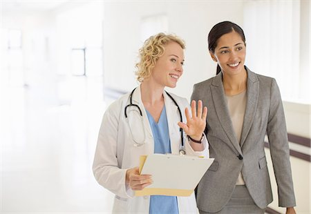 simsearch:6113-07146726,k - Doctor and businesswoman talking in hospital corridor Stock Photo - Premium Royalty-Free, Code: 6113-07146791