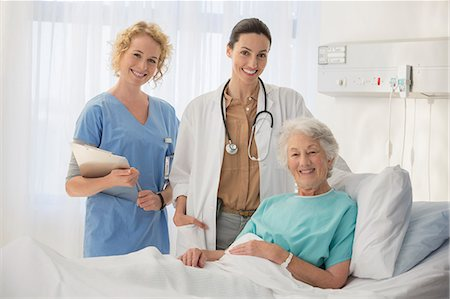 simsearch:6113-07146726,k - Doctor, nurse and senior patient smiling in hospital room Stock Photo - Premium Royalty-Free, Code: 6113-07146794