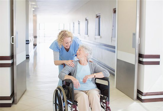 Nurse with aging patient in wheelchair in hospital corridor Stock Photo - Premium Royalty-Free, Image code: 6113-07146796