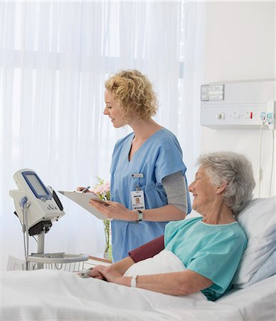 simsearch:6113-07146726,k - Nurse checking equipment in aging patient's hospital room Stock Photo - Premium Royalty-Free, Code: 6113-07146799