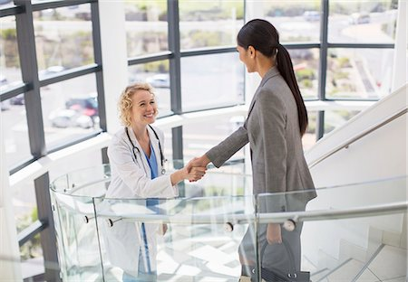 Doctor and businesswoman handshaking on stairs in hospital Stock Photo - Premium Royalty-Free, Code: 6113-07146711