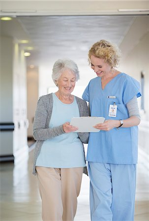 simsearch:6113-07146726,k - Nurse and aging patient reading chart in hospital corridor Stock Photo - Premium Royalty-Free, Code: 6113-07146726