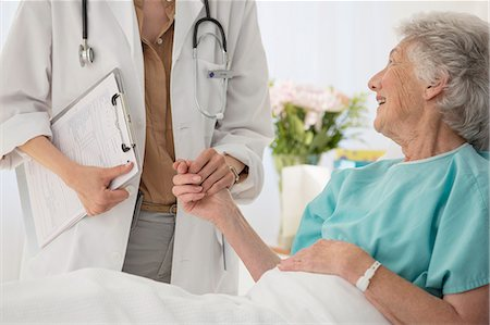simsearch:6113-07146726,k - Doctor and aging patient holding hands in hospital Stock Photo - Premium Royalty-Free, Code: 6113-07146729