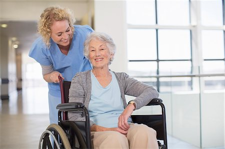 simsearch:6113-07146726,k - Nurse and aging patient smiling in hospital corridor Stock Photo - Premium Royalty-Free, Code: 6113-07146733