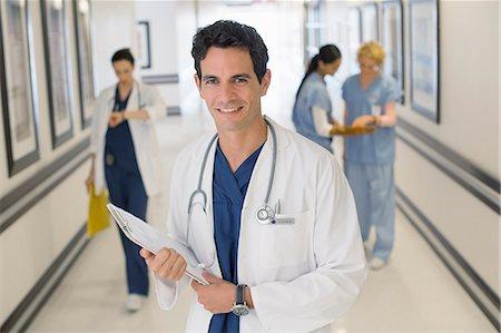 Portrait of smiling doctor in hospital corridor Stock Photo - Premium Royalty-Free, Code: 6113-07146730