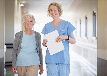 Portrait of smiling nurse and senior patient in hospital corridor Stock Photo - Premium Royalty-Free, Code: 6113-07146736