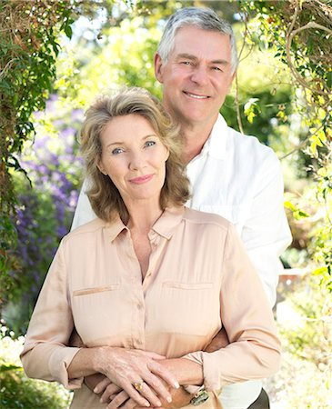 Portrait of smiling senior couple hugging outdoors Stock Photo - Premium Royalty-Free, Code: 6113-07146845