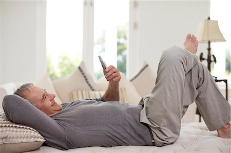 Senior man using cell phone on bed Stock Photo - Premium Royalty-Free, Code: 6113-07146874