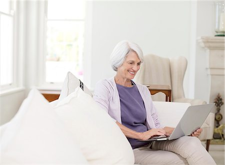 Senior woman using laptop on sofa in living room Stock Photo - Premium Royalty-Free, Code: 6113-07146889