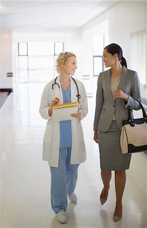 simsearch:6113-07146726,k - Doctor and businesswoman walking in hospital corridor Stock Photo - Premium Royalty-Free, Code: 6113-07146807