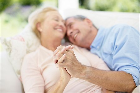 Senior couple holding hands on sofa Stock Photo - Premium Royalty-Free, Code: 6113-07146828