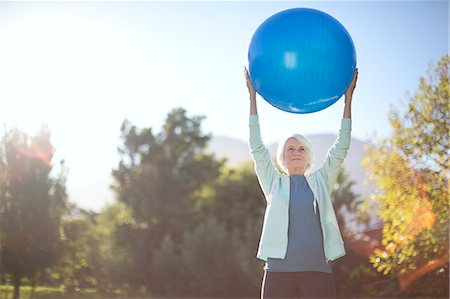 Senior woman holding fitness ball in park Stock Photo - Premium Royalty-Free, Code: 6113-07146837