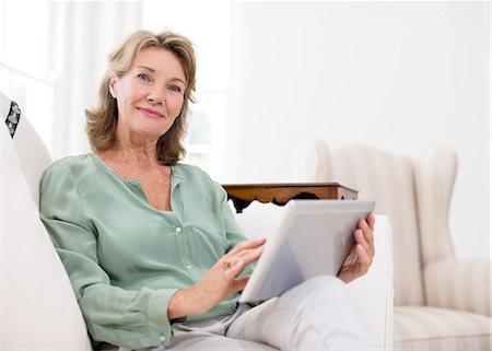 Portrait of senior woman using digital tablet on sofa Stock Photo - Premium Royalty-Free, Code: 6113-07146924