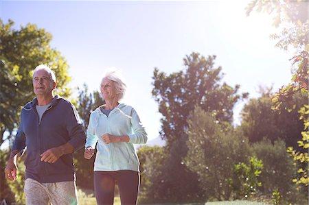 Senior couple running in park Stock Photo - Premium Royalty-Free, Code: 6113-07146934