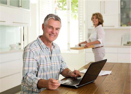 Portrait of smiling senior man using laptop in kitchen Stock Photo - Premium Royalty-Free, Code: 6113-07146939