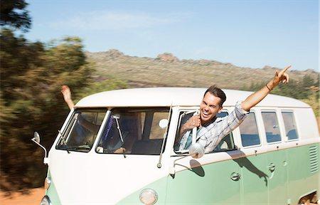 road trip - Man leaning head out camper van window on rural road Stock Photo - Premium Royalty-Free, Code: 6113-07147067