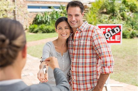sold sign - Realtor giving couple keys to new house Stock Photo - Premium Royalty-Free, Code: 6113-07147148