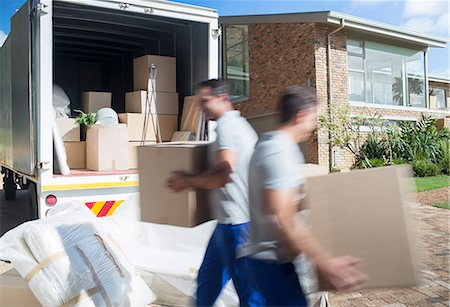 Movers carrying cardboard boxes in driveway Stock Photo - Premium Royalty-Free, Code: 6113-07147152