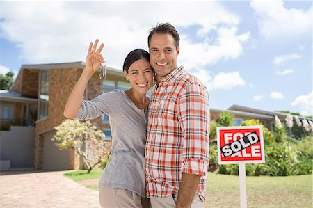sold sign - Portrait of smiling couple holding keys in front of new house Stock Photo - Premium Royalty-Free, Code: 6113-07147156
