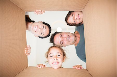 Family looking down at camera through cardboard box Stock Photo - Premium Royalty-Free, Code: 6113-07147167