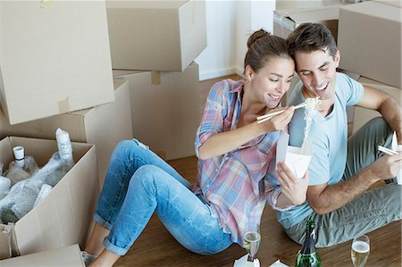 Couple sharing Chinese take out food in new house Stock Photo - Premium Royalty-Free, Code: 6113-07147171
